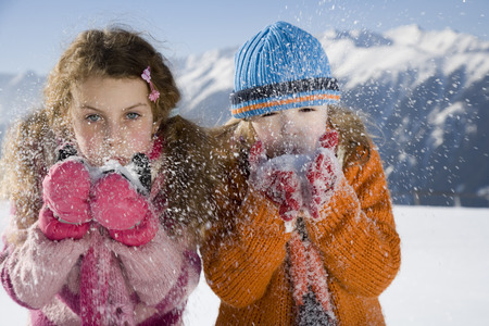 Children blowing snow in hands, Luesener Alm, Dolomite Alps, South Tyrol, Italy