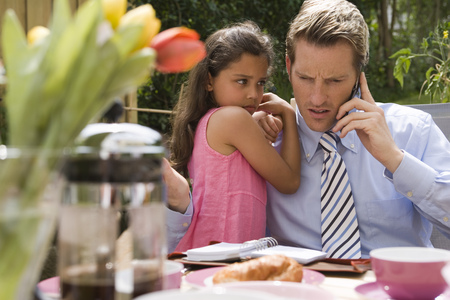 Father hugging daughter and talking on cell phone