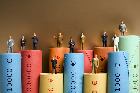 Rolls of assorted Euro coins with businessmen figurines LANG_EVOIMAGES