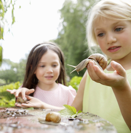 Young girls playing with snails