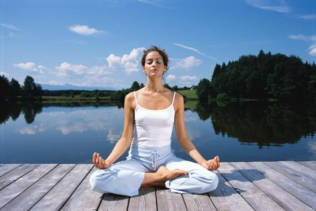 Young woman meditating on dock