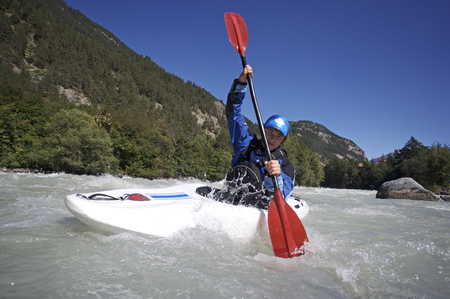 Person paddling kayak in whitewater LANG_EVOIMAGES