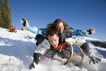 Couple riding on sled, Luesener Alm, Dolomite Alps, South Tyrol, Italy
