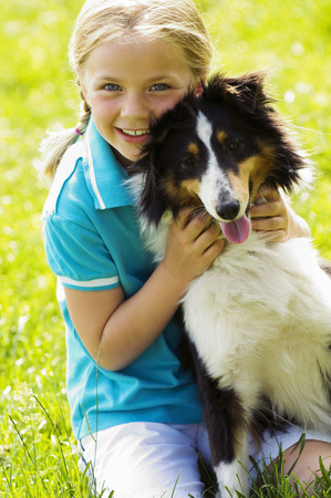 Young girl hugging dog outdoors LANG_EVOIMAGES