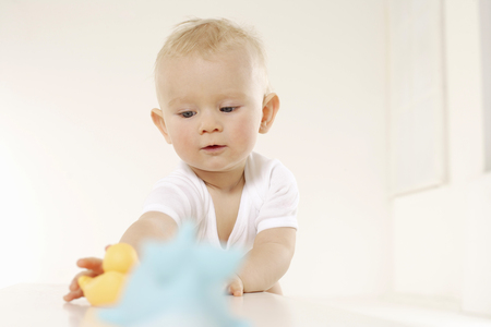 Baby reaching for toy duck