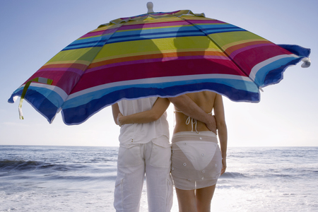Couple standing under umbrella at beach