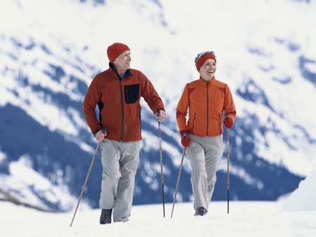 Senior couple walking with ski poles in snow LANG_EVOIMAGES
