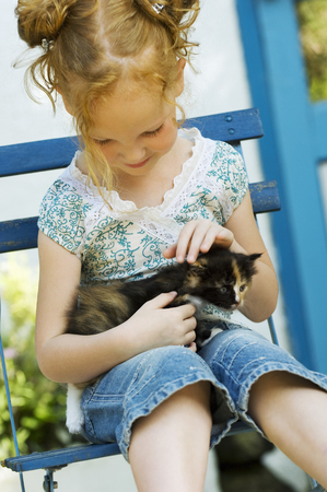 Young girl sitting in chair with kitten outdoors LANG_EVOIMAGES
