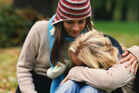 Young woman comforting friend outdoors in Autumn
