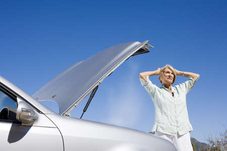 Senior woman experiencing car trouble, standing beside open bonnet with head in hands