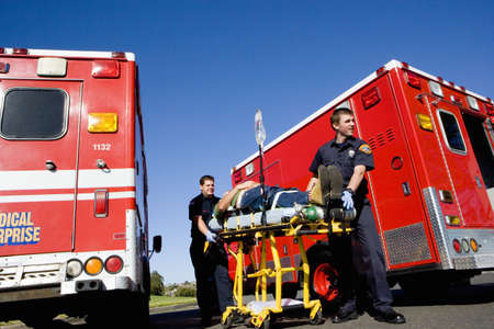 Paramedics with man on stretcher by ambulances, low angle view LANG_EVOIMAGES