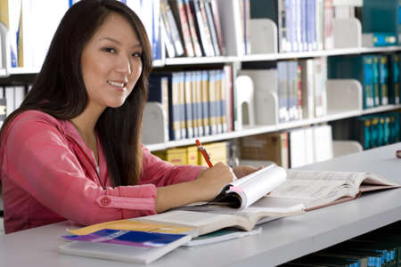 Woman studying in library, smiling, portrait, close-up