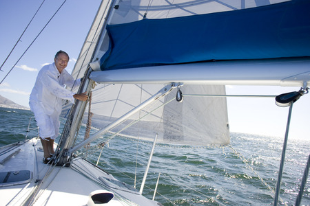 Mature man standing on deck of yacht out at sea, making adjustments to rigging, smiling, side view, portrait (tilt)