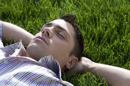 Man lying on grass, hands behind head, eyes closed, close-up