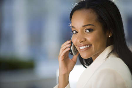 Businesswoman using mobile phone, smiling, side view, portrait LANG_EVOIMAGES