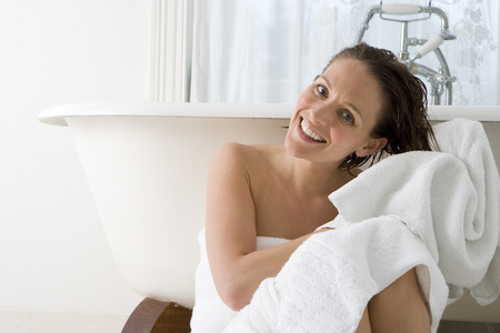 Young woman in bath towel drying hair with towel by bath, smiling, portrait LANG_EVOIMAGES