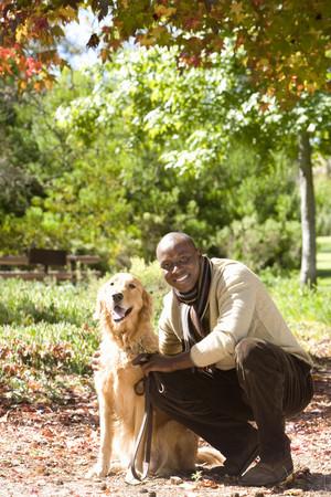 Man crouching beside golden retriever in autumn park, smiling, portrait