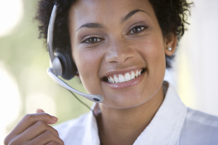 Young businesswoman wearing headset, smiling, portrait LANG_EVOIMAGES