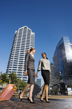 Two businesswomen walking with luggage along city street, smiling, side view (surface level)