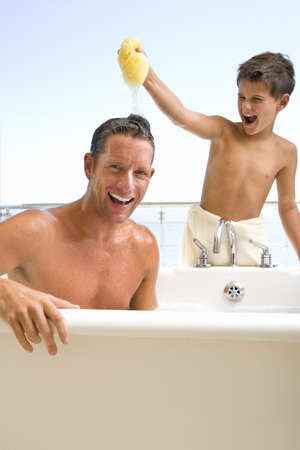 Father and son in bathroom, son (6-8) holding sponge above fathers head, smiling
