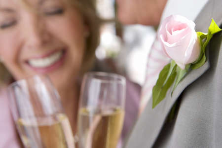 Senior bride and groom drinking champagne, smiling, close-up of glasses LANG_EVOIMAGES