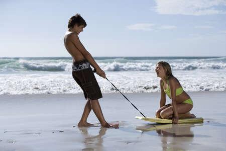 Teenage couple (13-15) playing on beach, boy pulling girl along sand on bodyboard, profile
