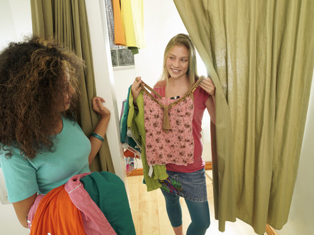 Two teenage girls (15-17) trying on new clothes in clothes shop fitting room, smiling LANG_EVOIMAGES
