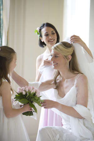 30s bride indoors being attended to by bridesmaids, one holding bouquet