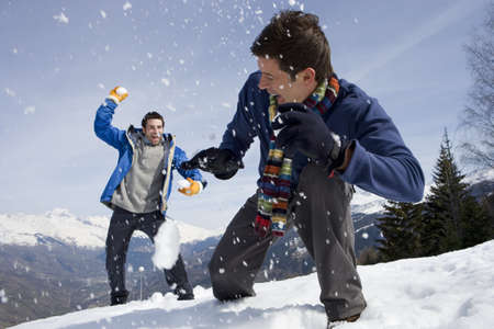 Two young men having snow fight in snow field LANG_EVOIMAGES
