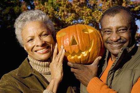 Senior couple holding aloft Jack OLantern pumpkin, smiling, front view, close-up, portrait