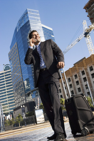 Businessman standing with luggage on city street, using mobile phone, smiling (surface level, tilt)