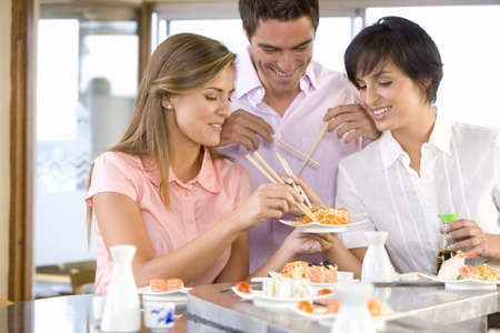 Three friends eating in sushi bar, smiling LANG_EVOIMAGES
