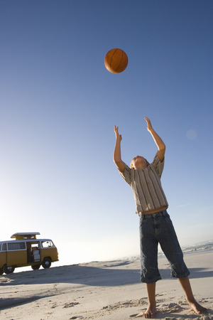 Boy (6-8) on beach throwing ball up, camper van in background, low angle view LANG_EVOIMAGES