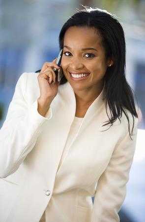 Businesswoman using mobile phone, smiling, portrait