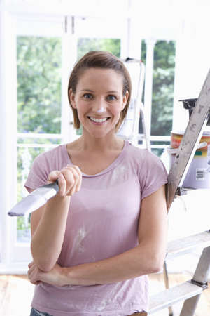 Young woman with paintbrush by ladder, smiling, portrait