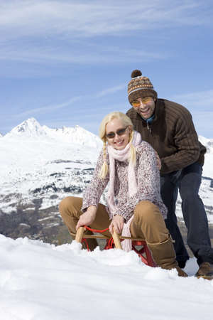 Young couple on sled in snow, wearing sunglasses, smiling, portrait, mountain range in background