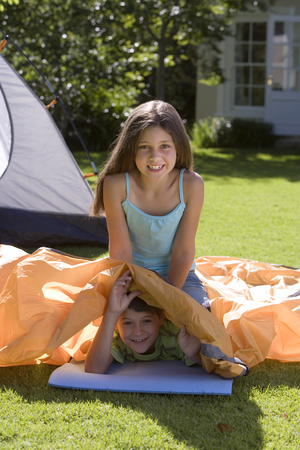 Brother and sister (8-10) assembling tent on garden lawn, girl sitting on top of boy lying beneath orange outer tent canvas, smiling, portrait LANG_EVOIMAGES