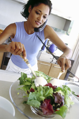 Woman talking on the telephone while preparing salad