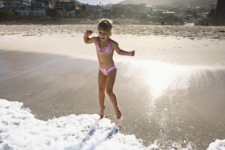 South Africa, Cape Town, girl (6-8) playing in surf at beach, resort in background LANG_EVOIMAGES