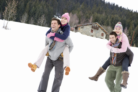 Two young couples smiling in snow field, men carrying women on backs, cottage in background, low angle view LANG_EVOIMAGES