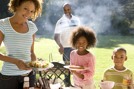 Family of four having barbeque, smiling, portrait LANG_EVOIMAGES