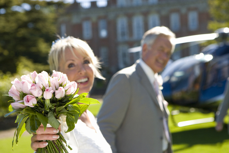 Bride with father by helicopter, smiling, focus on bouquet LANG_EVOIMAGES