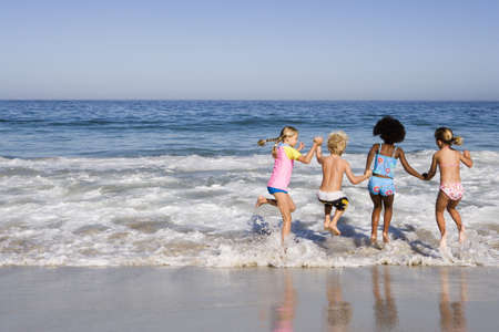 Four children (6-10) playing in Atlantic surf at beach, side by side, rear view LANG_EVOIMAGES