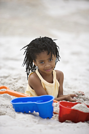 Girl (5-7) playing on sandy beach with bucket and spade, smiling, portrait LANG_EVOIMAGES