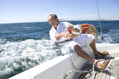 Mature man sitting on deck of yacht out at sea, leaning over side of boat, turning rope pulley, smiling LANG_EVOIMAGES