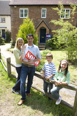 Family of four by fence by house, father holding sold sign, smiling, portrait LANG_EVOIMAGES
