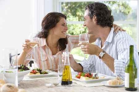 Couple embracing at lunch table, smiling at each other