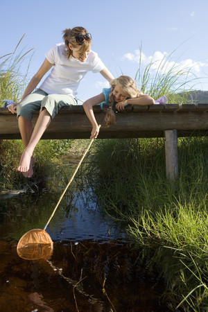 Mother and daughter (7-9) fishing above stream on small wooden footbridge, girl holding fishing net, smiling