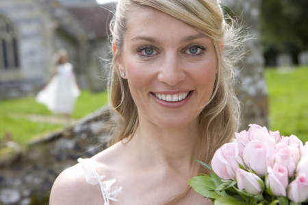 Close-up of bride with bouquet of flowers, smiling, portrait LANG_EVOIMAGES