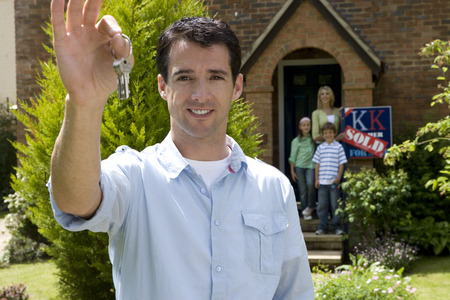 Young man outside house holding up key, family in doorway in background, portrait
